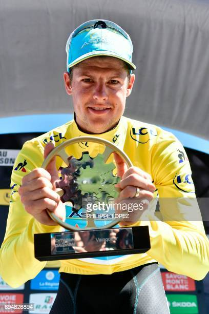 Denmark's Jakob Fuglsang celebrates his overall leader yellow jersey on the podium at the end of the 115 km eighth and last stage of the 69th edition...