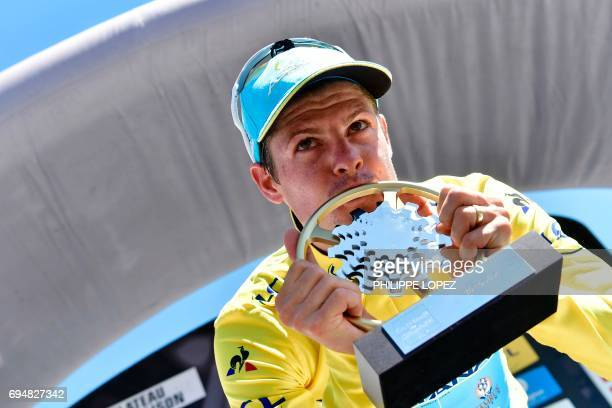 TOPSHOT Denmark's Jakob Fuglsang kisses his trophy as he celebrates his overall leader yellow jersey on the podium at the end of the 115 km eighth...