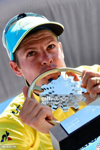 Denmark's Jakob Fuglsang kisses his trophy as he celebrates his overall leader yellow jersey on the podium at the end of the 115 km eighth and last...