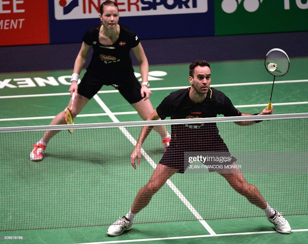 Denmark's Joachim Nielsen (front), flanked by Denmark's Christina Pedersen (rear), hits a shot against Dutch players Jacco Arends and Selena Piek during the 2016 European Badminton Championships mix double semi-final match between Denmark and Netherlands, on April 30, 2016 in Mouilleron-le-Captif, western France. / AFP / JEAN