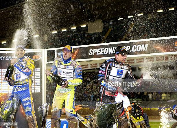 Denmark's Kenneth Bjerre sprays champagne after winning the Swedish Speedway Grand Prix with second placed Tomasz Gollob of Poland and third placed...