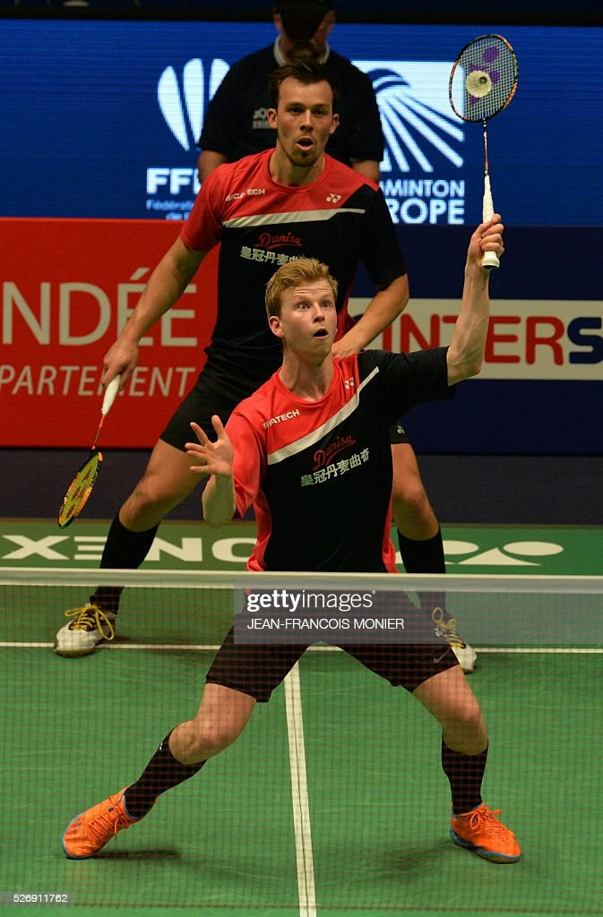 Denmark's Kim Astrup (front) flanked by teammate Anders Skaarup Rasmussen, hits a return during their 2016 European Championships Badminton double men's final match, on May 1, 2016 in Mouilleron-le-Captif, western France. / AFP / JEAN