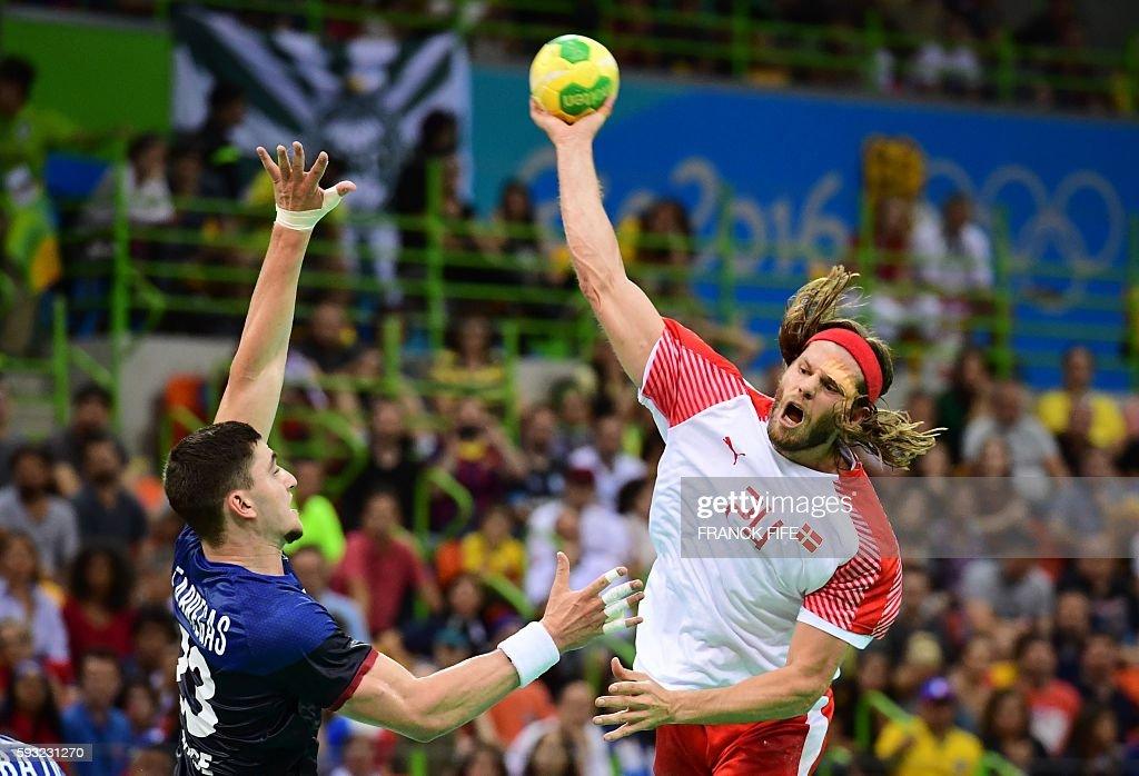 TOPSHOT Denmark's left back Mikkel Hansen attempts a shot on goal over France's pivot Ludovic Fabregas during the men's Gold Medal handball match...