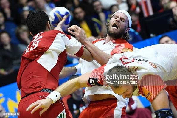 TOPSHOT Denmark's left back Mikkel Hansen is being held back during the 25th IHF Men's World Championship 2017 eighth final handball match Hungary vs...