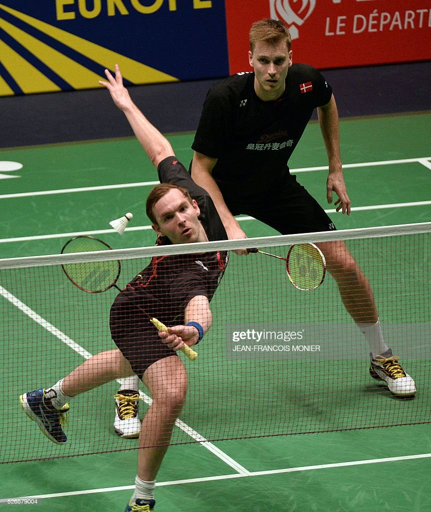 Denmark's Mads Conrad-Petersen (front), flanked by teammate Pieler Kolding, hits a return against British's players Marcus Elis and Chriss Langridge during the 2016 European Badminton Championships Men's double semi-final match between Denmark and England, on April 30, 2016 in Mouilleron-le-Captif, western France. / AFP / JEAN