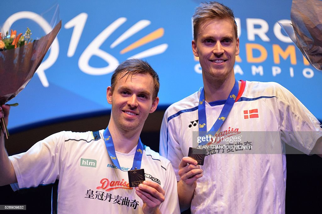 Denmark's Mads Conrad-Petersen (L), flanked by teammate Pieler Kolding, react on the podium after winning to Denmark's Kim Astrup and teammate Anders Skaarup Rasmussen, during their 2016 European Championships Badminton double men's final match on May 1, 2016 in Mouilleron-le-Captif, western France. / AFP / JEAN