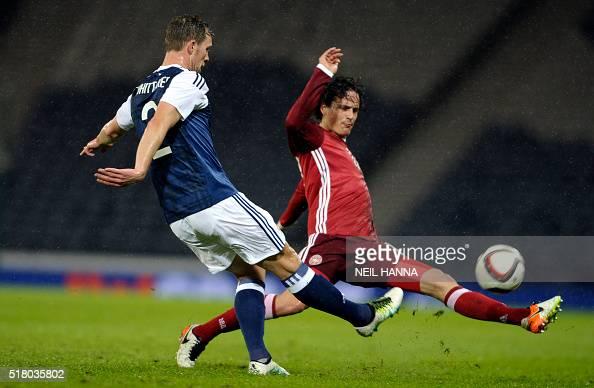 Denmark's midfielder Thomas Delaney leaps accress to block Scotland's defender Steven Whittaker during the international friendly football match...