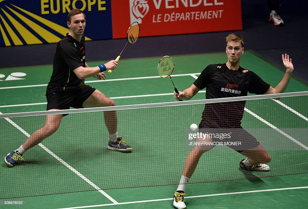 Denmark's Pieler Kolding (front), flanked by teammate Mads Conrad-Petersen, prepares to hit a return against British players Marcus Ellis and Chriss Langridge during the 2016 European Badminton Championships Men's double semi-final match between Denmark and England, on April 30, 2016 in Mouilleron-le-Captif, western France. / AFP / JEAN