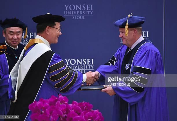 Denmark's Prime Minister Lars Lokke Rasmussen shakes hands with Yonsei University president Kim YongHak as he receives an honorary degree of Doctor...