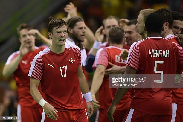 Denmark's right wing Lasse Svan and teammates celebrate their victory and qualification for the semis at the end of the men's quarterfinal handball...