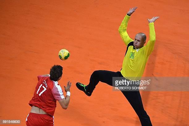 Denmark's right wing Lasse Svan shoots at Slovenia's goalkeeper Gorazd Skof during the men's quarterfinal handball match Denmark vs Slovenia for the...