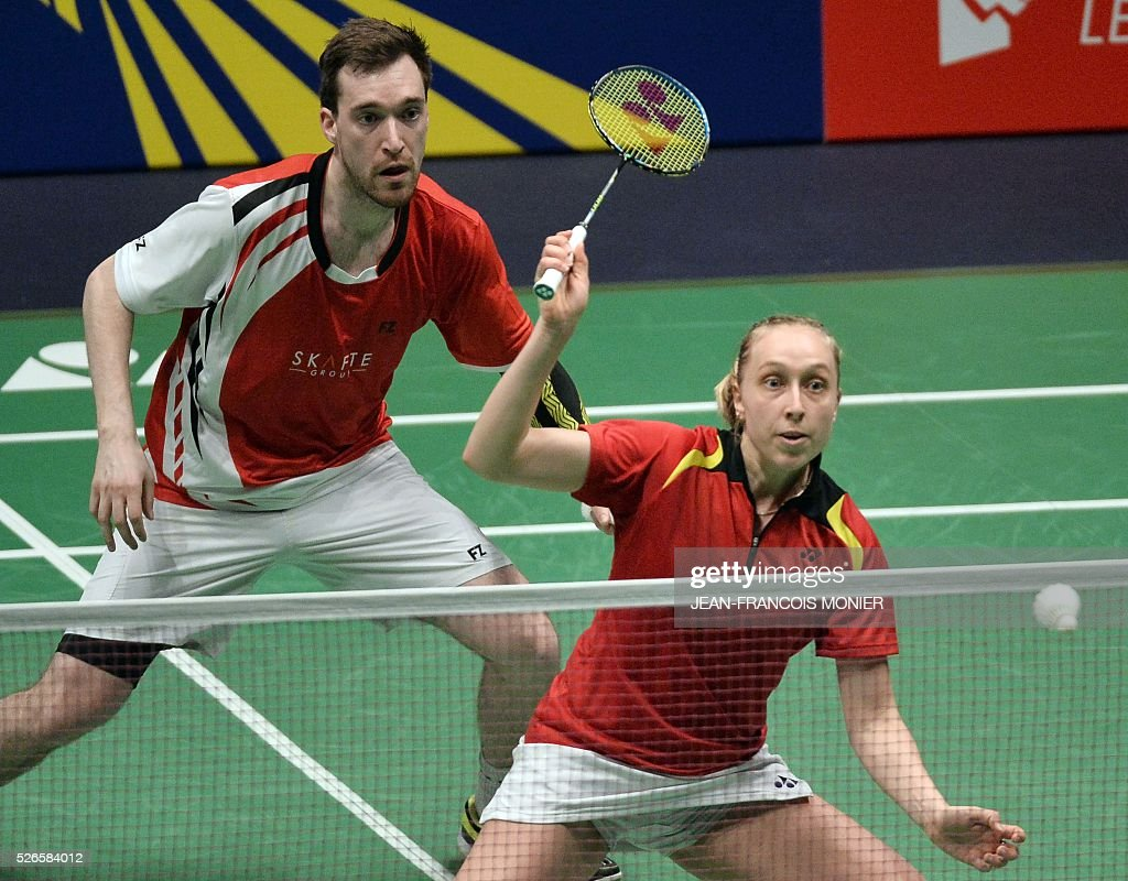 Denmark's Sara Thygesen (front) flanked by teammate Niclas Nohr (rear) prepares to hit a return against Denmark's players Mathias Christiansen and Lena Grebak during the 2016 European Badminton Championships mix double semi-final match between Denmark and Denmark, on April 30, 2016 in Mouilleron-le-Captif, western France. / AFP / JEAN