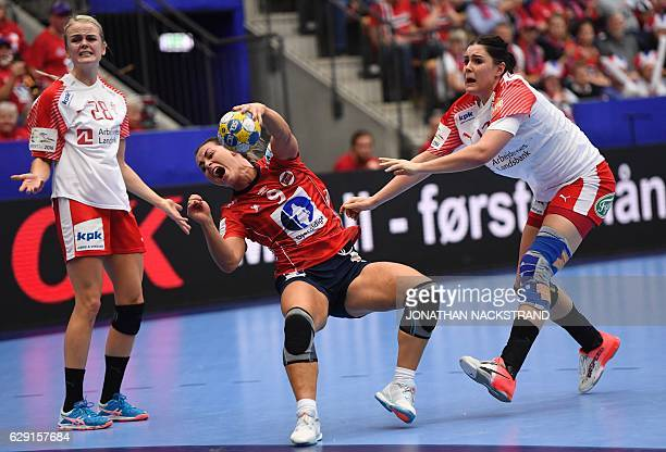 Denmark's Stine Bodholt Nielsen reacts as she tries to stop Norway's Nora Mork as she prepares to throw the ball during the Women's European Handball...