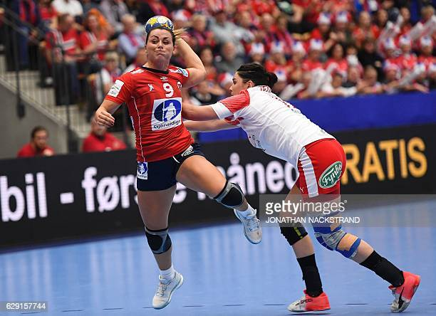 Denmark's Stine Bodholt Nielsen tries to stop Norway's Nora Mork as she prepares to throw the ball during the Women's European Handball Championship...