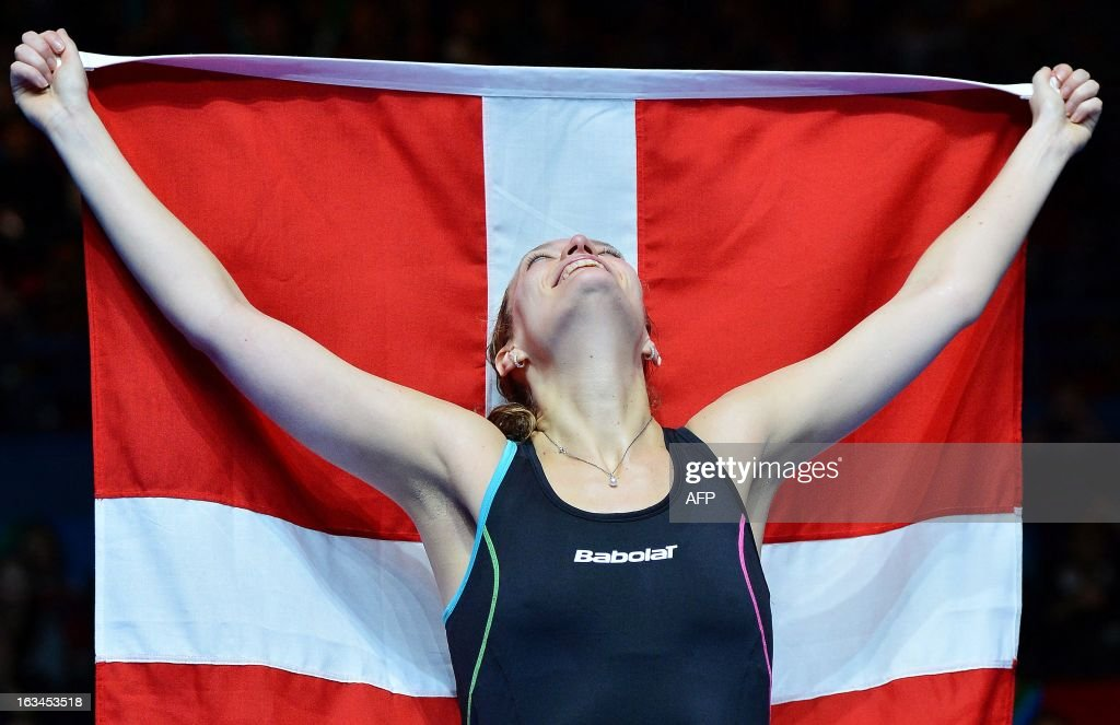 Denmark's Tine Baun holds her national flag as she celebrates after winning the All England Open Badminton Championships women's singles final match against Thailand's Intanon Ratchanok in Birmingham, central England, on March 10, 2013.