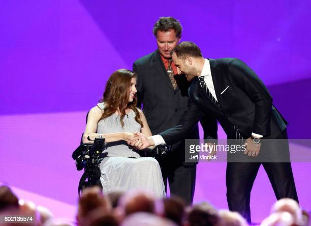 Denna Laing and Nick Foligno of the Columbus Blue Jackets shake hands onstage during the 2017 NHL Awards Expansion Draft at TMobile Arena on June 21...