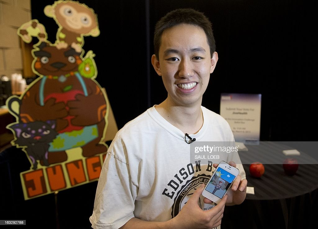Dennis Ai, a student at Northwestern University and founder of Jivehealth, uses an iPhone to demonstrate a game app to be sold at the Apple App store, during the Partnership for a Healthier America summit in Washington, DC, March 7, 2013. Ai, is the founder of Jivehealth, a company developed to encourage healthy eating habits in children. AFP PHOTO / Saul LOEB