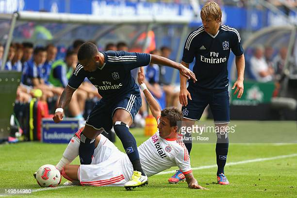 Dennis Aogo of Hamburg and Mario Mandzukic of Bayern Muenchen battle for the ball during the LIGA total Cup 3rd place match between Hamburger SV and...