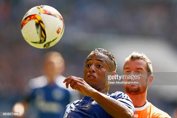 Dennis Aogo of Schalke clears the ball away from Marcel Heller of Darmstadt during the Bundesliga match between FC Schalke 04 and SV Darmstadt 98...