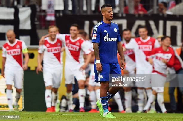 Dennis Aogo of Schalke reacts as Yannick Gerhardt of Koeln celebrates his team's second goal with team mates during the Bundesliga match between 1 FC...