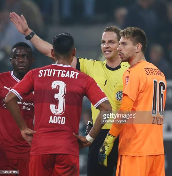 Dennis Aogo of Stuttgart and goalkeeper RonRobert Zieler of Stuttgart argue with referee Soeren Storks after he awards a penalty to Moenchengladbach...