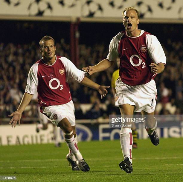 Dennis Bergkamp of Arsenal celebrates scoring the opening goal during the UEFA Champions League match between Arsenal and Borussia Dortmund at...