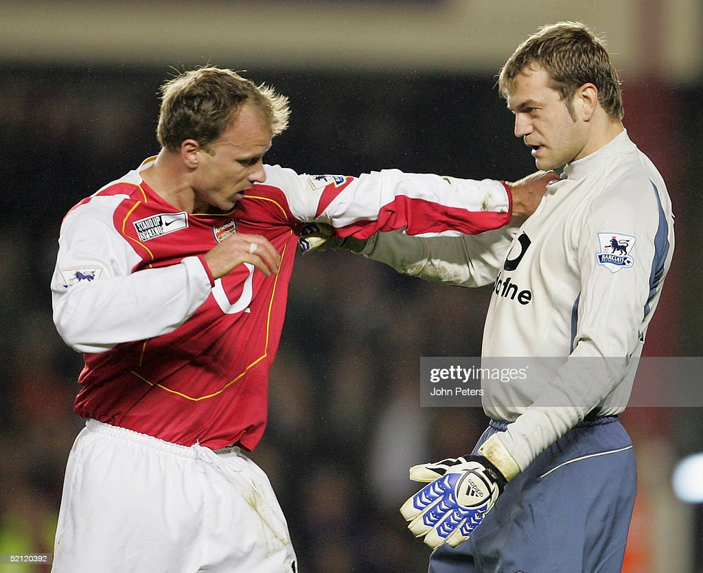 Dennis Bergkamp of Arsenal clashes with Roy Carroll of Manchester United during the Barclays Premiership match between Arsenal and Manchester United on February 1, 2005 at Highbury in London, England.