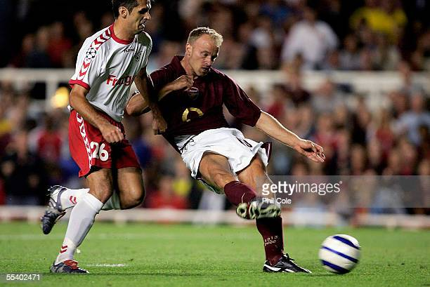 Dennis Bergkamp of Arsenal holds off the challange from Selver Hodzic of FC Thun to score the winning goal during the Champions League Group B match...