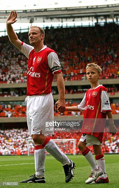 Dennis Bergkamp waves as he leads his son Mitchell onto the pitch to say goodbye to his fans after the testimonial match at Emirates stadium in north...