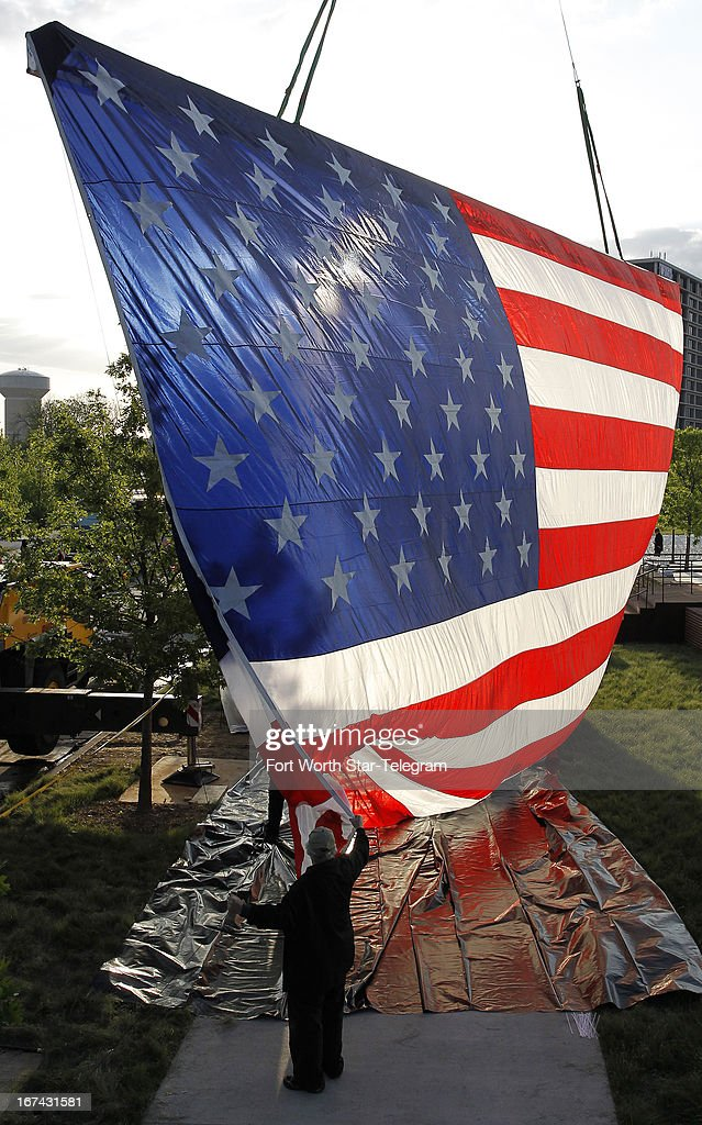 Dennis Courtney, with Showcall (the museum's opening show production company) holds on the ropes of a huge American Flag being raised near the site of the dedication ceremonies for the new George W. Bush Presidential Center in Dallas, Texas, Thursday, April 25, 2013.
