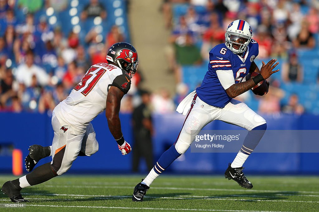 Dennis Dixon of the Buffalo Bills runs past Larry English of the Tampa Bay Buccaneers during the second half at Ralph Wilson Stadium on August 23...
