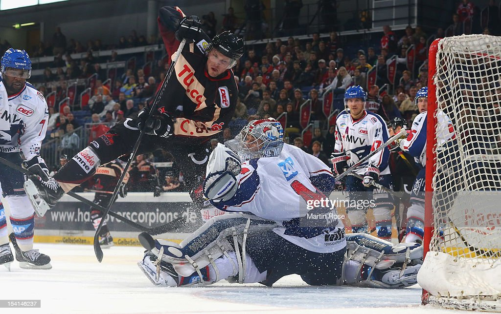Dennis Endras goaltender of Mannheim save the shot of Andreas Morczinietz of Hannover during the DEL match between Hannover Scorpions and Adler...