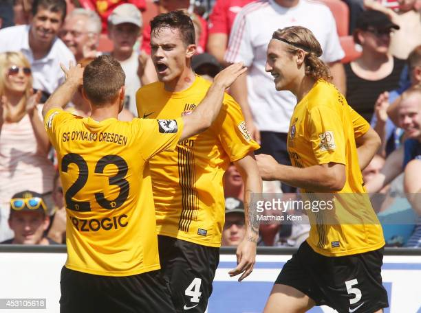 Dennis Erdmann of Dresden jubilates with team mates after scoring the first goal during the third league match between FC Energie Cottbus and SG...