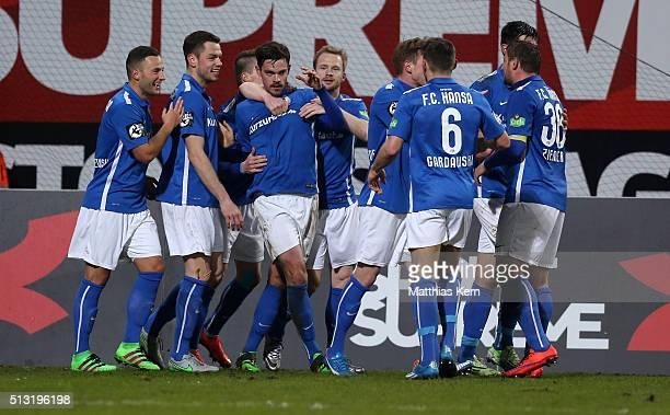 Dennis Erdmann of Rostock jubilates with team mates after scoring the first goal during the third league match between FC Hansa Rostock and Holstein...