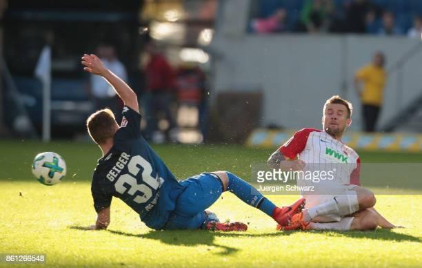 Dennis Geiger of Hoffenheim tackles Daniel Baier of Augsburg during the Bundesliga match between TSG 1899 Hoffenheim and FC Augsburg at Wirsol...