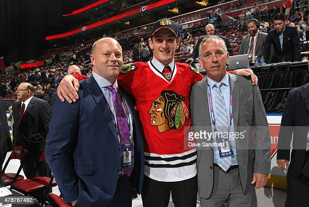 Dennis Gilbert 91st overall pick of the Chicago Blackhawks stands on the draft floor with Stan Bowman and Mark Kelley during the 2015 NHL Draft at...