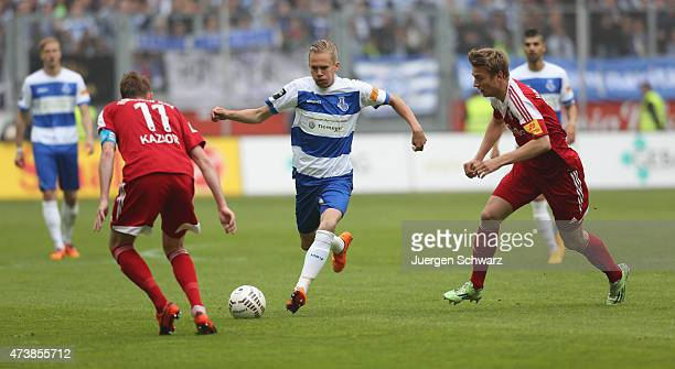 Dennis Grote of Duisburg controls the ball near Rafael Kazior and Hauke Wahl of Kiel during the 3rd Bundesliga match between MSV Duisburg and...