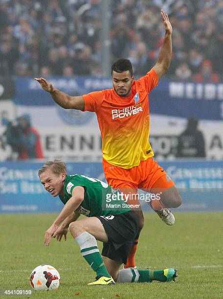 Dennis Grote of Muenster challenges Phil OfosuAyeh of Duisburg during the Third League match between Preussen Muenster and MSV Duisburg at...