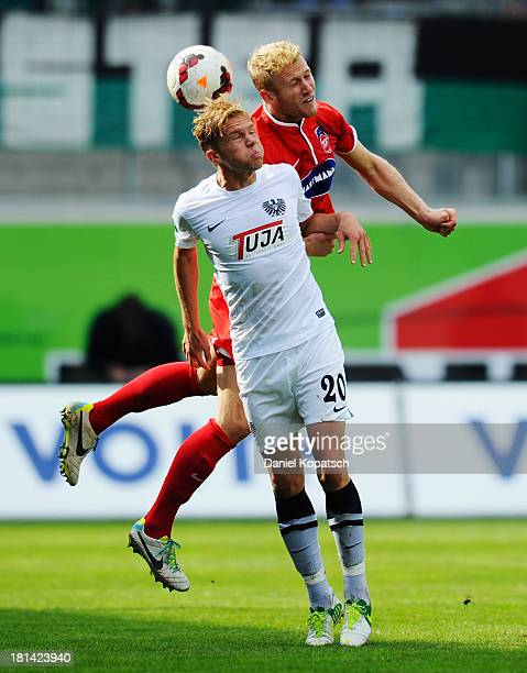 Dennis Grote of Muenster jumps for a header with Sebastian Griesbeck of Heidenheim during the third Bundesliga match between 1 FC Heidenheim and...