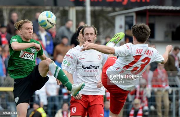 Dennis Grote of Muenster Mario Neunaber andJimPatrick Mueller of Regensburg compete for the ball during the Third League match between Jahn...