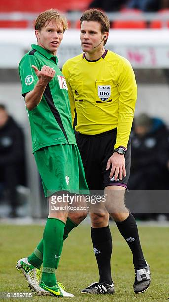 Dennis Grote of Muenster reacts next to Referee Felix Brych during the third Bundesliga match between 1 FC Heidenheim and Preussen Muenster at...