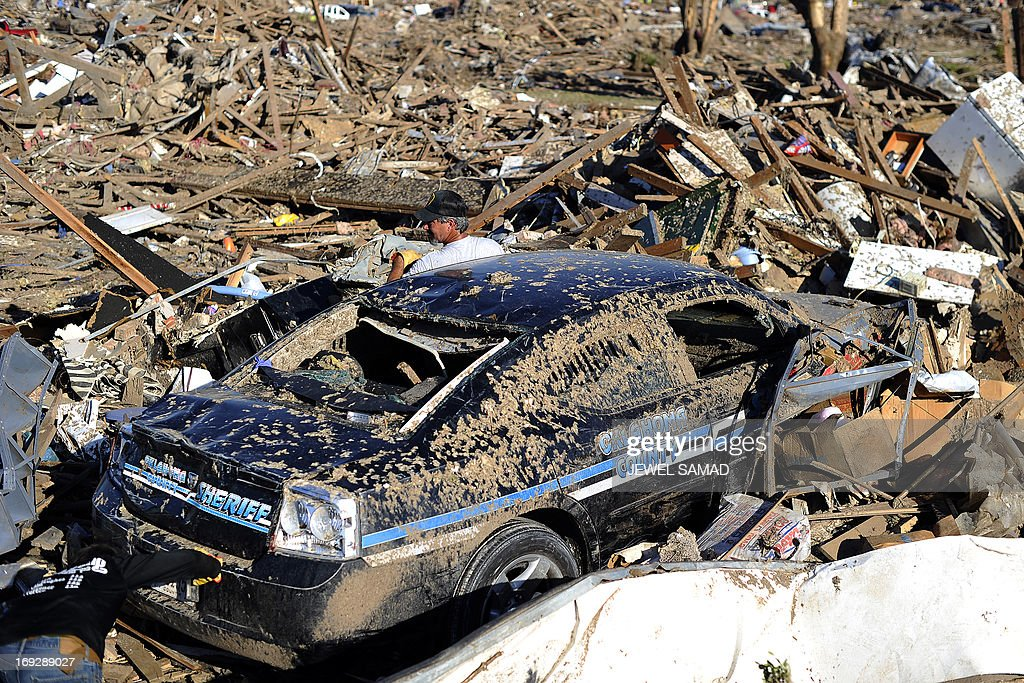 Dennis Guarnera (C) tries to dig out his brother's police car from the debris of their tornado-devastated home on May 22, 2013 in Moore, Oklahoma. As rescue efforts in Oklahoma wound down, residents turned to the daunting task of rebuilding a US heartland community shattered by a vast tornado that killed at least 24 people. The epic twister, two miles (three kilometers) across, flattened block after block of homes as it struck mid-afternoon on May 20, hurling cars through the air, downing power lines and setting off localized fires in a 45-minute rampage. AFP PHOTO/Jewel Samad