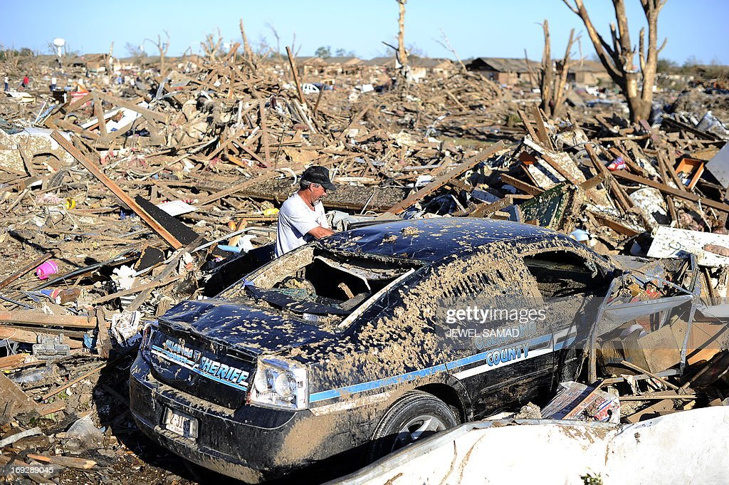 Dennis Guarnera tries to dig out his brother's police car from the debris of their tornado devastated home on May 22, 2013 in Moore, Oklahoma. As rescue efforts in Oklahoma wound down, residents turned to the daunting task of rebuilding a US heartland community shattered by a vast tornado that killed at least 24 people. The epic twister, two miles (three kilometers) across, flattened block after block of homes as it struck mid-afternoon on May 20, hurling cars through the air, downing power lines and setting off localized fires in a 45-minute rampage. AFP PHOTO/Jewel Samad