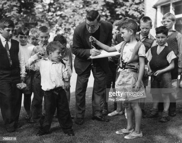 Dennis Holmes and George Daly play 'conkers' in a match adjudicated by the Reverend R Barington Rector of Milton church Gravesend Kent
