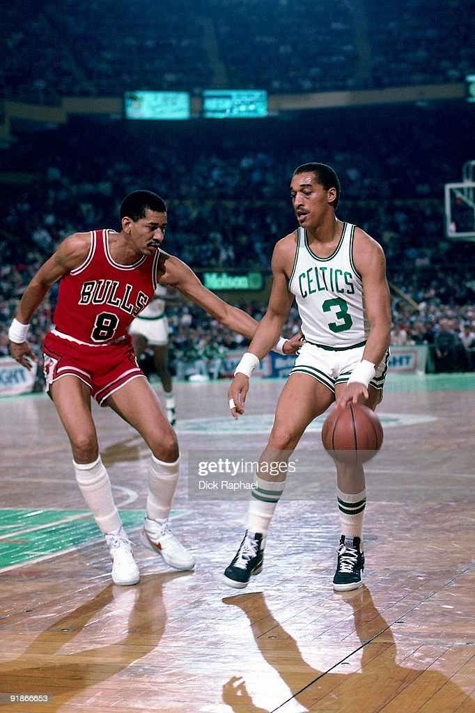 Dennis Johnson of the Boston Celtics moves the ball up court against George Gervin of the Chicago Bulls during a game played in 1986 at the Boston...
