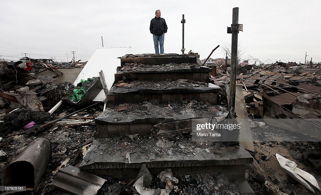 Dennis Kane stands above the charred remains of his destroyed home in the hard hit Breezy Point neighborhood on December 7, 2012 in the Queens borough of New York City. Breezy Point, home to many New York City firefighters and police, lost 111 homes in a fast moving fire during Superstorm Sandy with many more homes severely damaged from flooding.