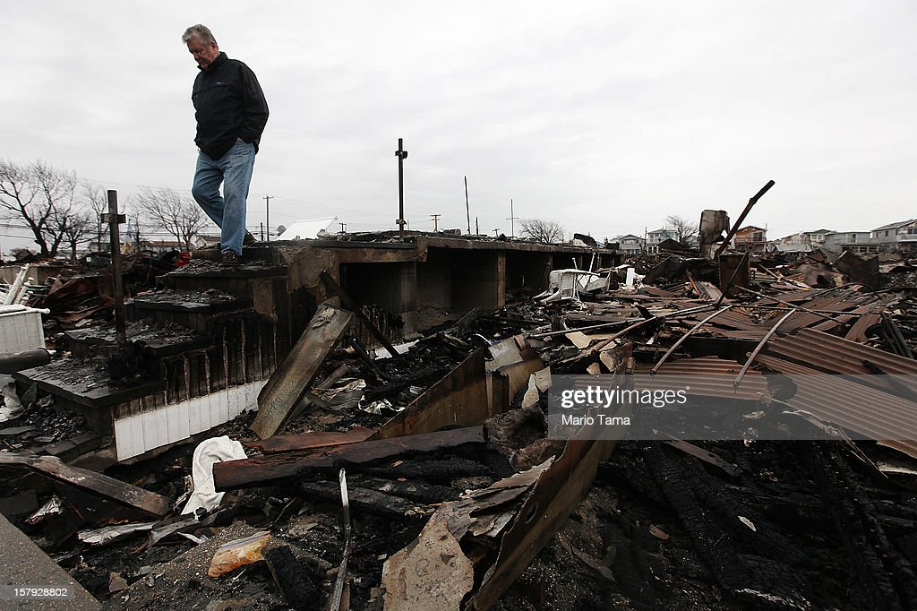 Dennis Kane walks above the charred remains of his destroyed home in the hard hit Breezy Point neighborhood on December 7, 2012 in the Queens borough of New York City. Breezy Point, home to many New York City firefighters and police, lost 111 homes in a fast moving fire during Superstorm Sandy with many more homes severely damaged from flooding.