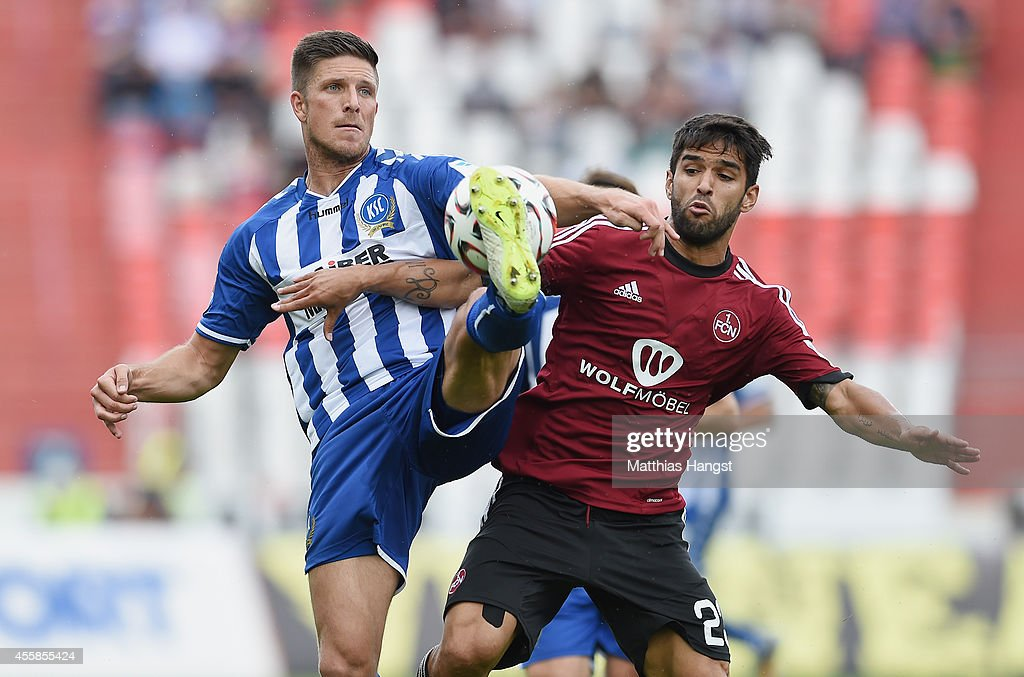 Dennis Kempe of Karlsruhe and Candeias of Nuernberg compete for the ball during the Second Bundesliga match between Karlsruher SC and 1 FC Nuernberg...