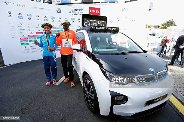 Dennis Kimetto of Kenya poses with his new world record time and the women's first place winner Tirfi Tsegaye of Ethiopia after winning the 41th BMW...