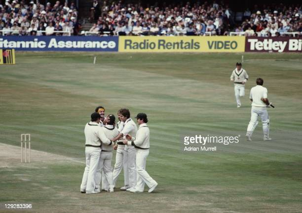 Dennis Lillee of Australia congratulates team mate Rodney Marsh on his world record for wicket keeper catches after the dismissal of Ian Botham...